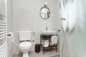Open shelving, neutral colors, and a clean design help small bathrooms feel bigger.